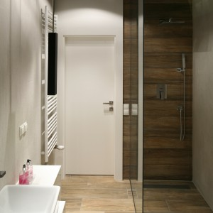 W wąskiej łazience strefę prysznica wydzielono za pomocą szklanej tafli. Odpływ liniowy umieszczony w posadzce to funkcjonalne rozwiązanie, które nie zmniejsza optycznie wnętrza. Projekt: Dominik Respondek. Fot. Bartosz Jarosz.