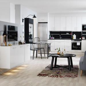 Jasny parkiet, biała zabudowa firmy Marbodal i dużo gustownych dodatków sprawiają, że ta kuchnia otwarta na salon prezentuje się niezwykle efektownie. Detale w industrialnym klimacie idealnie wpisują się w skandynawską stylistykę. Fot. Marbodal.