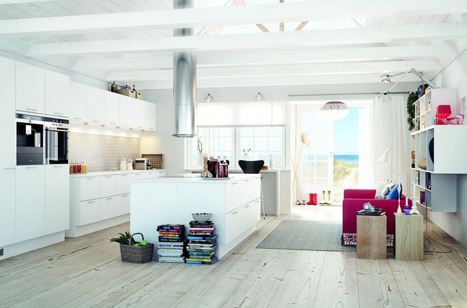 Rozświetlona naturalnym światłem kuchnia. Biała zabudowa kuchenna marki HTH utrzymana w całości w bieli jest ocieplona wizualnie przez podłogę w jasnym kolorze drewna. Aranżację dopełniają odsłonięte belki stropowe pomalowane na biało. Fot. HTH.