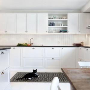 Meble, ściana, a nawet podłoga - wszystkie te elementy wnętrza są wykonane w śnieżnej bieli. Ociepla ją drewniany stół, a kontrastuje blat w bardzo ciemny odcieniu brązu. Funkcjonalna zabudowa z licznymi szufladami i praktycznymi górnymi półkami gwarantuje wygodne użytkowanie kuchni. Fot. Ballingslov.