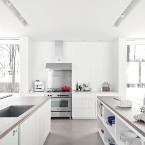 Zaprojektowana przez kanadyjską pracownię laSHED Architecture kuchnia to piękny przykład stylistyki skandynawskiej. Duże okna pozbawione firanek wpuszczają do środka maksimum naturalnego światła, które odbija się od białych ścian i mebli. Całość bardzo delikatnie ociepla surowe drewno. Projekt: laSHED Architecture.