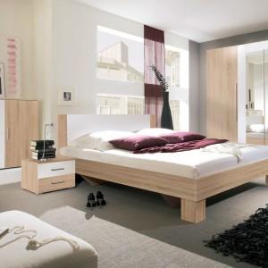 Sypialnia Vera marki Helvetia Wieruszów to połączenie nowoczesnej formy i trendu łączącego biel z drewnem. W kolekcji do wyboru jest wyjątkowo pojemna szafa, komoda oraz łóżka w dwóch wymiarach sprzedawane łącznie z parą szafek nocnych. Fot. Helvetia Wieruszów.