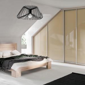 Przestrzeń w sypialni na poddaszu z powodzeniem można wykorzystać na garderobę. W części ograniczonej skosami można układać rzeczy na półkach, natomiast w wyższej - wieszać ją na wieszakach. Fot. Komandor.