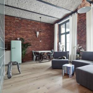 Dodatki w domu kojarzą się z industrialnymi wnętrzami nowojorskich loftów, podążając jednocześnie za najświeższymi desinerskimi tendencjami. Techniczna lampa w salonie ma modny w tym sezonie kolor złota, a w sąsiedztwie kuchni stanął kultowy stołek Oskara Zięty. Fot. RED Real Estate Development.