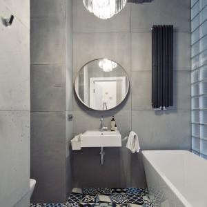 W łazience dominuje szarość, wprowadzona przez duże betonowe płyty. Z ich surowością kontrastuje dekoracyjny żyrandol w stylu glamour, a całość ożywia patchworkowa posadzka w etniczne wzory. Fot. RED Real Estate Development.