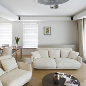 Elegancką strefę dzienną urządzono w jasnej palecie barw. Wygodne sofy organizują strefę wypoczynku, którą doświetlają wysokie okna. Projekt: Kamila Paszkiewicz. Fot. Bartosz Jarosz.