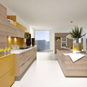 Nowoczesna kuchnia, w której meble w piaskowym kolorze drewna połączono z ciepłą żółcią, która dodatkowo wprowadza do wnętrza przytulny nastrój. Fot. Alno, meble z programu Alnosund.