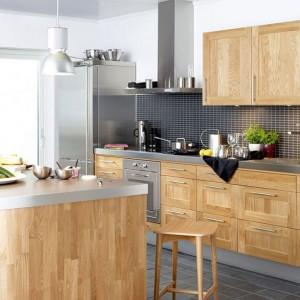 """Połączenie drewna i stali to uniwersalny i ponadczasowy zestaw. Frezowane fronty w ciepłym wybarwieniu nadają przestrzeni klasycyzujący charakter a stalowe blaty wprowadzają nowoczesny """"pazur"""". Fot. Ballingslov, kuchnia Studio."""