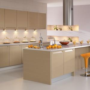 Kuchnia w kolorze drewna, której najefektowniejszym elementem są oryginalne uchwyty, wyżłobione we frontach mebli kuchennych. Nowoczesna i przytulna aranżacja. Fot. Atlas Kuchnie.