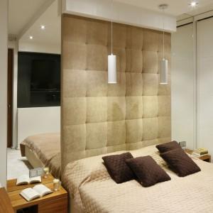Tapicerowana ściana za łóżkiem dodaje nowoczesnej aranżacji miękkości, koresponduje tez z elementami drewna. Niewielką przestrzeń powiększają optycznie tafle luster, zamocowane po obu stronach wezgłowia. Projekt: Michał Mikołajczak. Fot. Bartosz Jarosz.