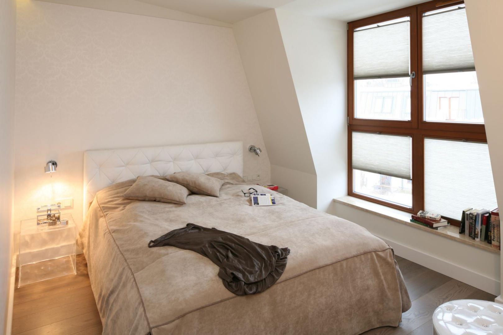 Beżowa narzuta na łóżko to, oprócz drewnianej podłogi, element wystroju, który nadaje wnętrzu spokojny wygląd sprzyjający wypoczynkowy. W tworzeniu kameralnego nastroju pomagają przyciemniane rolety okienne. Projekt: Małgorzata Borzyszkowska. Fot. Bartosz Jarosz.