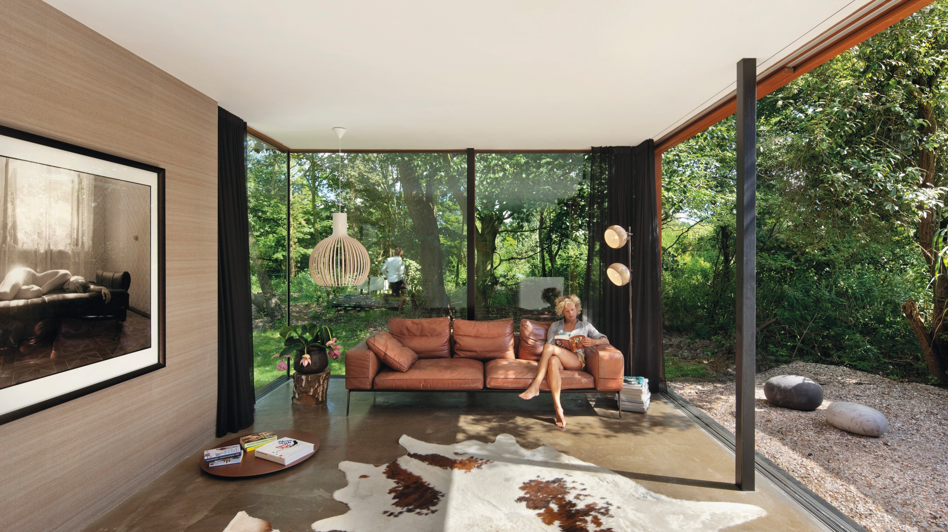 Dzięki ogromnym przeszkleniom ogród dosłownie wnika do wnętrza domu. Siedząc na kanapie w salonie możemy poczuć się jakbyśmy odpoczywali na tarasie. Projekt: Jeroen van Zwetselaar. Fot. Cornbread Works.