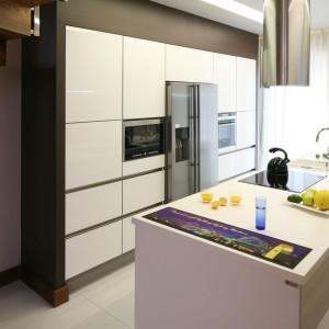 Dzięki przeniesieniu na wyspę strefy zmywania i gotowania, w tej kuchni zrezygnowano całkowicie z dolnych szafek. Wysoka zabudowa pokrywa niemal całą ścianę, a w nią wpasowano sprzęty AGD. Projekt: Chantal Springer. Fot. Bartosz Jarosz.