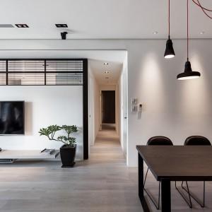 Ze strefy dziennej można bezpośrednio przejść do reszty pomieszczeń w mieszkaniu. Korytarz komunikuje część dzienną z sypialnią i łazienką. Projekt: Circle Huang i Gina Chou. Fot. Hey! Cheese.