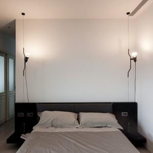 Zamiast tradycyjnych lampek nocnych, nad łóżkiem po obu stronach mebla zawisło ciekawe, delikatnie industrialne oświetlenie. Projekt: Circle Huang i Gina Chou. Fot. Hey! Cheese.