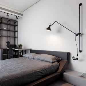 Jedną z sypialni połączono z domowym biurem. Dwojaki charakter przestrzeni sprawił, że lampka nocna jest utrzymana w nieco biurowym charakterze. Projekt: Circle Huang i Gina Chou. Fot. Hey! Cheese.