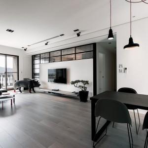 Ścianę, na której zainstalowano telewizor obudowano szklaną zabudową w kształcie litery L. Za nią skrywa się sypialnia z garderobą. Projekt: Circle Huang i Gina Chou. Fot. Hey! Cheese.