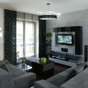 Nieduży salon urządzono w szarościach. W tym kolorze jest zarówno kamienna ściana za telewizorem, jak i tapicerowany w tkaninie narożnik. Projekt: Maciejka Peszyńsk-Drews. Fot. Bartosz Jarosz.
