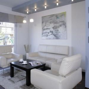 Nieduży salon urządzono w bieli. Strefę wypoczynkową organizuje klasyczny zestaw wypoczynkowy - dwa fotele plus sofa. Projekt: Lilianna Masewicz-Kowalska. Fot. Monika Filipiuk-Obałek.