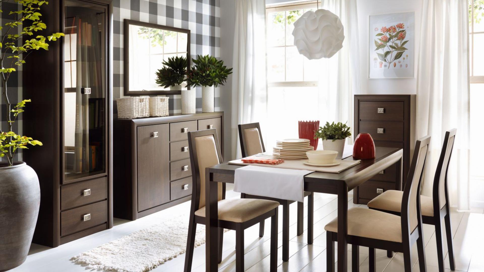 Meble z kolekcji Koen to klasyczne wzornictwo w nieco odświeżonej wersji. Uniwersalny design zamknięto w ciepłe, przytulne barwy koloru dąb canterbury. Drewno efektownie kontrastuje z metalowymi, srebrnymi uchwytami mebli. Fot. Black Red White.