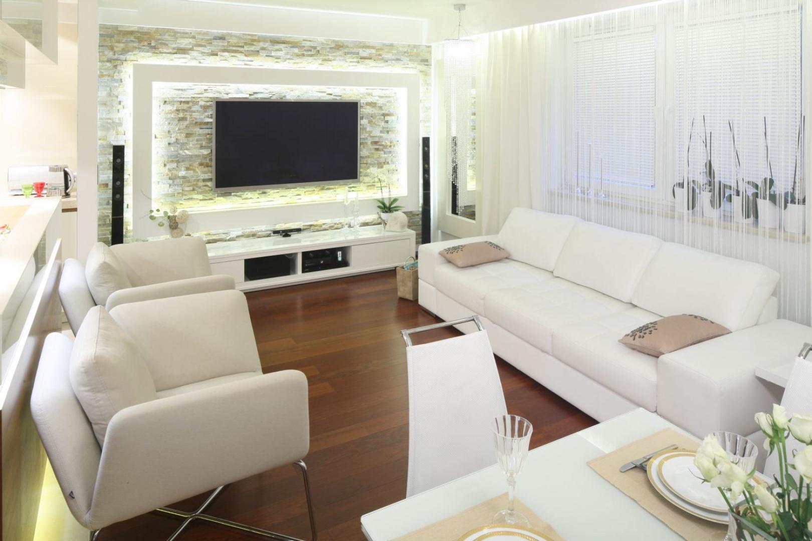 W niedużym salonie zdecydowano się na trzyosobową sofę, którą ustawiono wzdłuż okna. Do niej dobrano dwa wygodne fotele. Projekt: Małgorzata Mazur. Fot. Bartosz Jarosz.