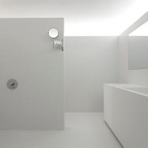Łazienka to nowoczesne, minimalistyczne kształty, zatopione w bieli. Jedynym, co urozmaica aranżację jest mozaika, przełamująca połacie śnieżnej barwy. Projekt: laSHED Architecture. Fot. Maxime Brouillet.