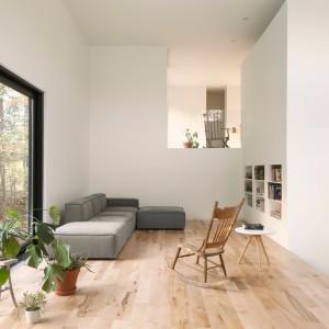 W domu dominują jasne barwy: biel ścian i sufitu, ocieplona drewnianą podłogą w jasnym wybarwieniu. Projekt: laSHED Architecture. Fot. Maxime Brouillet.