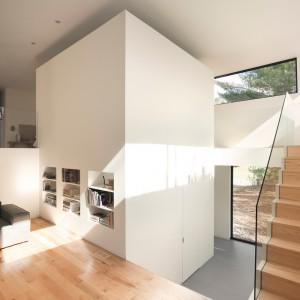 W zabudowie sąsiadującej z salonem urządzono praktyczne półki, służące za domową biblioteczkę. Projekt: laSHED Architecture. Fot. Maxime Brouillet.