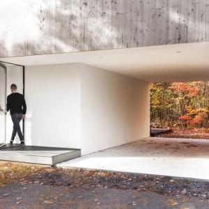 Z zewnątrz elewacje domu pokryto deskami, które ocieplają nowoczesną, minimalistyczną formę bryły budynku. Projekt: laSHED Architecture. Fot. Maxime Brouillet.