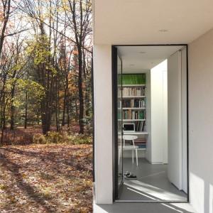 Większość pomieszczeń w domu ma duże okna, wyglądające na malowniczy krajobraz. Z domowego gabinetu można bezpośrednio udać się na świeże powietrze. Projekt: laSHED Architecture. Fot. Maxime Brouillet.