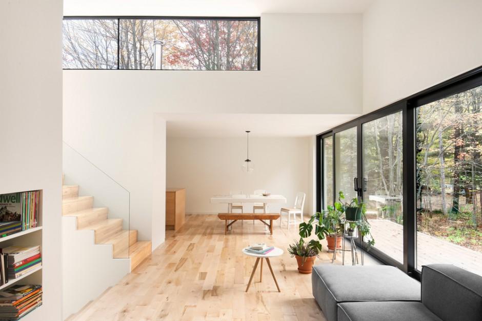 Duże panoramiczne przeszklenia poprowadzone od samej podłogi sprawiają, że dom jest otwarty na otaczający go krajobraz. Projekt: laSHED Architecture. Fot. Maxime Brouillet.