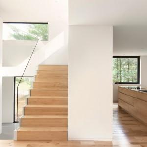 Do znajdującej się na piętrze sypialni prowadzą drewniane schody, które przesłania delikatnie szklana balustrada, nadająca przestrzeni lekkość. Projekt: laSHED Architecture. Fot. Maxime Brouillet.