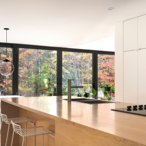 Obszerna wyspa kuchenna służy za powierzchnię roboczą, w obrębie której urządzono strefy zmywania i gotowania. Nowoczesna forma mebla zamknięta została w przytulny kolor drewna. Projekt: laSHED Architecture. Fot. Maxime Brouillet.