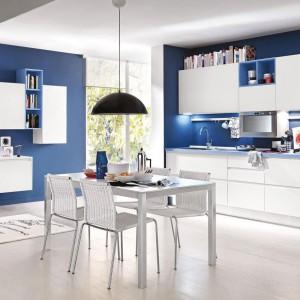Meble Linda pozwalają na idealne zestawienie zabudowy kuchennej z umeblowaniem salonu. Śnieżna biel pięknie współgra z wieloma kolorami, np. mocnym granatem. Całość tworzy harmonijną strefę dzienną. Fot. Cucine Lube.
