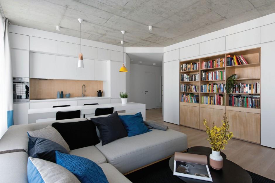 Przestrzeń dzienna łączy w sobie trzy funkcje: salonu, aneksu kuchennego oraz gabinetu. Pomieszczenie wypełniają jasne kolory, ocieplone drewnianymi elementami. Projekt: Normundas Vilkas. Fot. Leonas Garbacauskas.