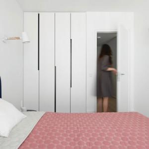 Ścianę w sypialni małżeńskiej zdobi zabudowa, wpasowana we wnękę w taki sposób, że razem z drzwiami tworzy równą powierzchnię. Minimalizm rozwiązania urozmaica asymetryczny wzór frontów. Projekt: Normundas Vilkas. Fot. Leonas Garbacauskas.