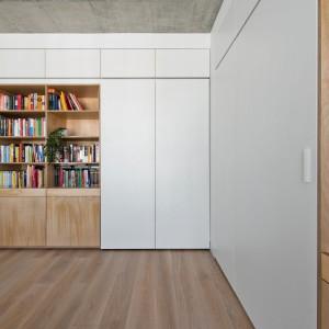 Z salonu można bezpośrednio przejść do pokoju dziecięcego. Pomieszczenia oddzielają białe drzwiczki, wykonane z takiego samego materiału, jak zabudowa meblowa, co sprawia, że są niemal niewidoczne i nie zaburzają aranżacji przestrzeni dziennej. Projekt: Normundas Vilkas. Fot. Leonas Garbacauskas.