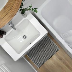 Ograniczona przestrzeń łazienki zaowocowała dużymi połaciami białych powierzchni, które optycznie powiększyły wnętrze. Ocieplają ją drewniane akcenty w postaci podłogi i ramy lustra. Projekt: Normundas Vilkas. Fot. Leonas Garbacauskas.
