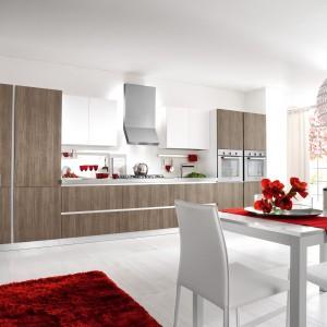 Elegancka zabudowa kuchenna na jedną ścianę z frontami w przytulnym wybarwieniu drewna i dwiema górnymi szafkami w kolorze złamanej bieli. Po obu stronach kuchnię zamykają słupki z wbudowanym sprzętem AGD. Fot. Home Cucine.