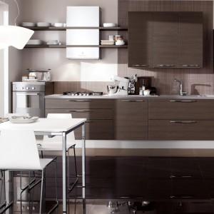Meble na jedną ścianę w kolorze drewna w ciemnym, czekoladowym wybarwieniu. Zestawienie poszczególnych elementów zabudowy w asymetryczny sposób nadaje jej oryginalny, nowoczesny charakter. Ciemne fronty zestawiono z otwartymi półkami nad blatem. Fot. Veneta Cucine, model Carrera.