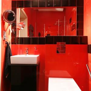 Spora tafla lustra oraz płytki w wysokim połysku sprawiają, że mała łazienka zyskuje nieco przestrzeni. Wszechobecną czerwień przełamują pojedyncze płytki o lustrzanych lub czarnych powierzchniach. Projekt: Beata Ignasiak. Fot. Bartosz Jarosz.