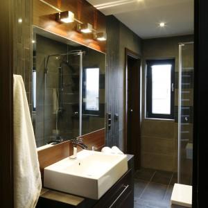 W tej łazience wszystko służy optycznemu powiększeniu przestrzeni - poziome pasy z płytek, mozaika z małych prostokątów oraz lustra. Na pierwszy rzut oka trudno uwierzyć, że pomieszczenia jest szerokie zaledwie na 1,5 metra. Projekt: Marta Kilan. Fot. Bartosz Jarosz.