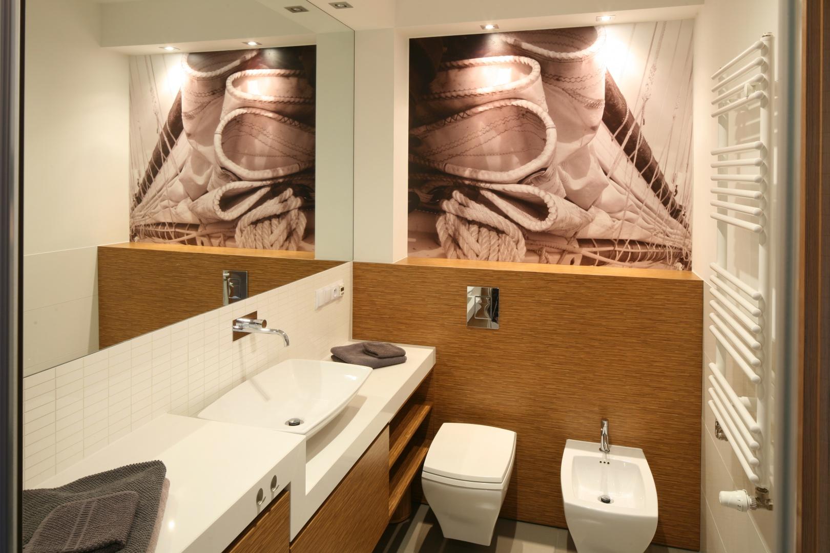 Łazienka jest mała, wydaje się jednak dwukrotnie większa za sprawą ogromnego lustra nad umywalką. Wyjątkową dekoracją jest fototapeta z żaglami nadrukowana na PCV. Projekt: Małgorzata Galewska. Fot. Bartosz Jarosz.