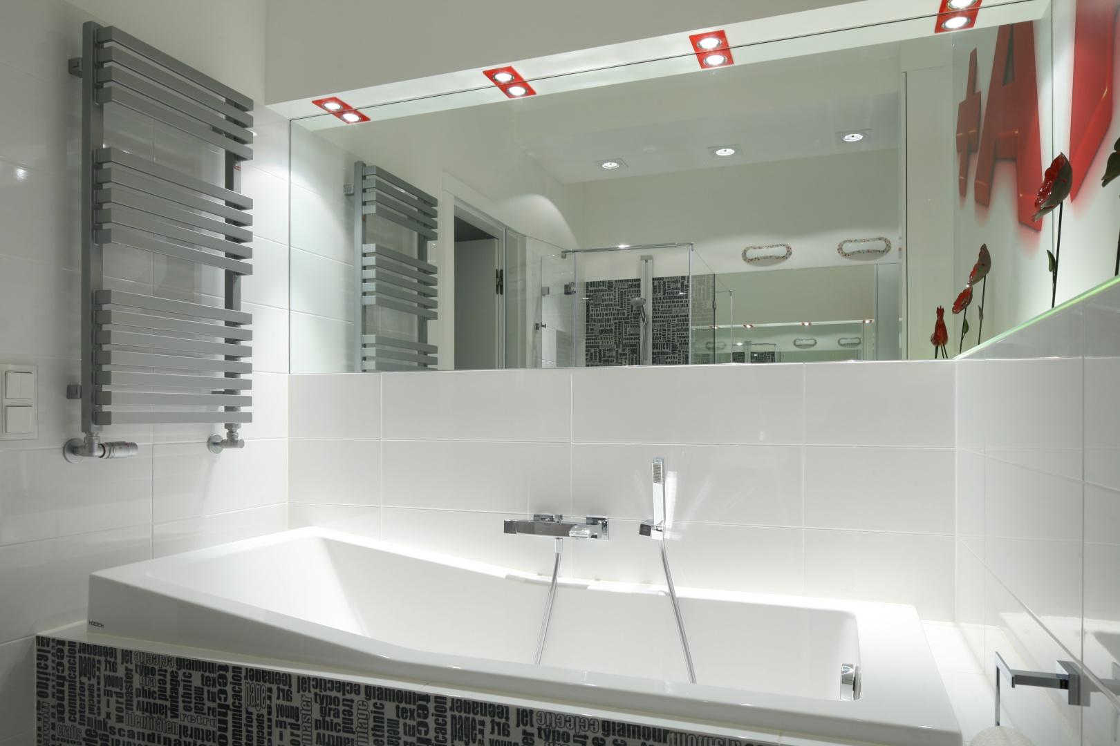 Tuż nad wanną zamontowano dużą taflę lustra, która optycznie powiększyła łazienkę przy sypialni. Szary grzejnik idealnie współgra z płytkami z graficznymi dekorami. Projekt: Katarzyna Mikulska-Sękalska. Fot. Bartosz Jarosz.