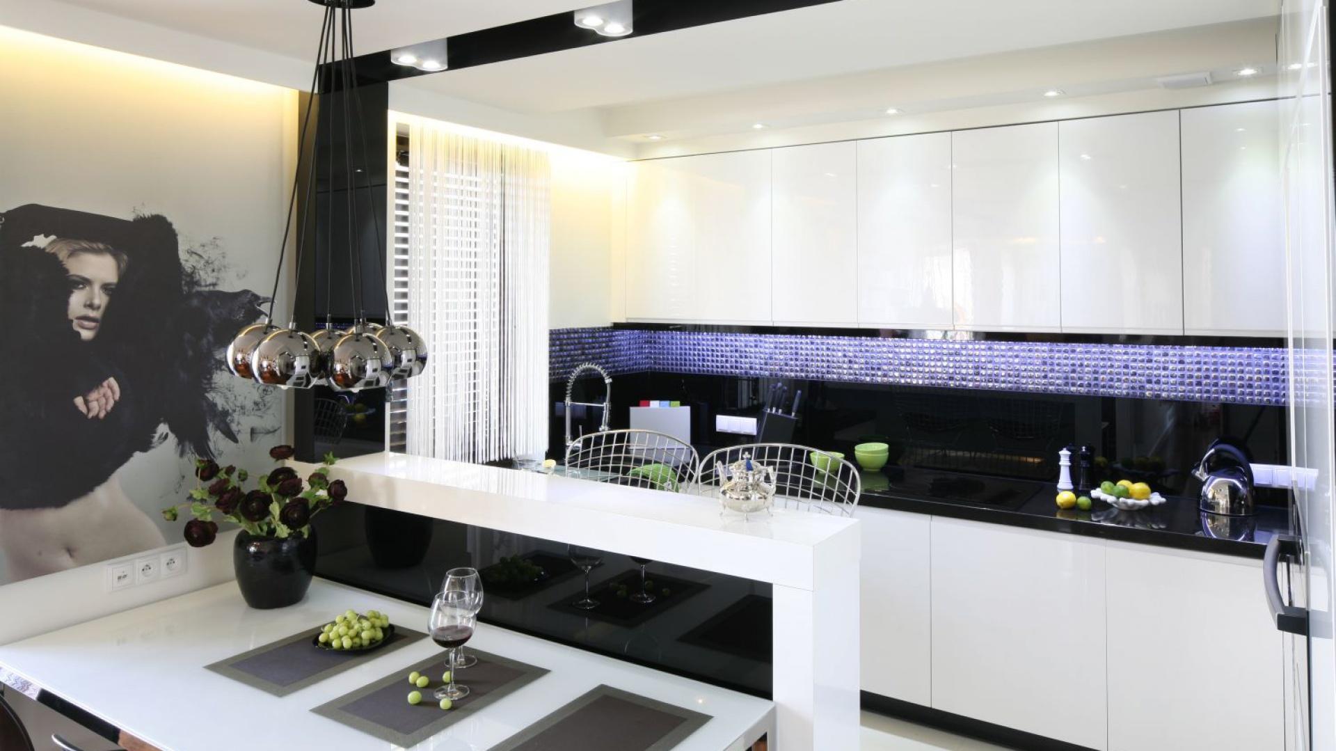 W tej eleganckiej czarno-białej kuchni ścianę nad blatem pokrywa szklana mozaika. Niepodświetlona ma czarny kolor, pod wpływem oświetlenia mieni się różnymi odcieniami. Projekt: Małgorzata Mazur. Fot. Bartosz Jarosz.