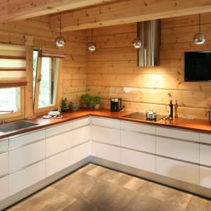 W tym pięknym, drewnianym domu, ściany w kuchni pokrywają naturalne, drewniane bale, przykryte przeźroczystym szkłem. Projekt: Tomasz Motylewski i Marek Bernatowicz. Fot. Bartosz Jarosz.