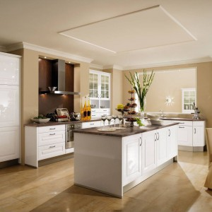 Piękna, klasyczna kuchnia wykończona na wysoki połysk. Fronty mebli zdobią eleganckie frezowania i dekoracyjne uchwyty, a całość wieńczy blat z efektem kamienia. Fot. Wellmann, meble z programu 528 Polaris.