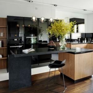 Nowoczesną formę mebli kuchennych zamknięto w szlachetne wykończenie z naturalnego forniru, połączonego z czarnym lakierem. Czerń nadaje zabudowie elegancki charakter, a naturalne drewno ją ociepla. Fot. Zajc Kuchnie, model Z1.