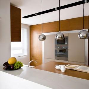 Na tle wysokiej zabudowy, w dużej mierze wykończonej w ciepłym kolorze drewna wyróżniają się trzy stalowe, kuliste klosze. Stanowią one nowoczesny, chłodny akcent w kuchni. Projek: Monika Kossakowska.