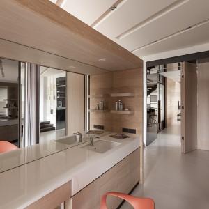 Toaletka z dużym lustrem została również wyposażona w umywalkę, w której pani domu może się odświeżyć przed pójściem spać w sypialni, schowanej za przegrodą. Projekt: Circle Huang&Gina Chiu. Fot. Hey! Cheese.